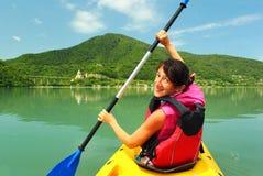 Młodej kobiety kayaker wioślarstwo na Jinvali jeziorze, Ananuri, Gruzja Fotografia Stock
