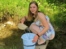 Młodej kobiety kolekcjonowania woda od naturalnej wiosny zdjęcia stock