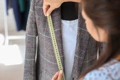 Młodej kobiety krawieccy bierze pomiary kurtka w atelier zdjęcie stock