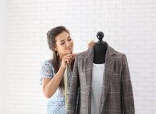 Młodej kobiety krawieccy bierze pomiary kurtka w atelier fotografia stock