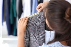 Młodej kobiety krawieccy bierze pomiary kurtka w atelier obraz royalty free