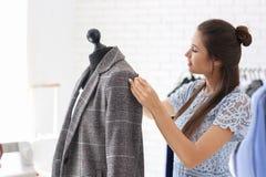 Młodej kobiety krawieccy bierze pomiary kurtka w atelier fotografia royalty free