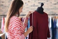 Młodej kobiety krawieccy bierze pomiary suknia na mannequin w atelier zdjęcie royalty free