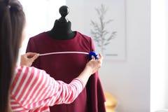 Młodej kobiety krawieccy bierze pomiary suknia na mannequin w atelier fotografia stock