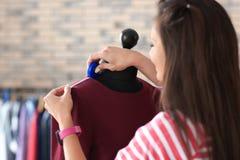 Młodej kobiety krawieccy bierze pomiary suknia na mannequin w atelier zdjęcie stock