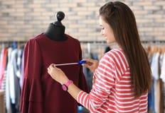 Młodej kobiety krawieccy bierze pomiary suknia na mannequin w atelier obraz royalty free