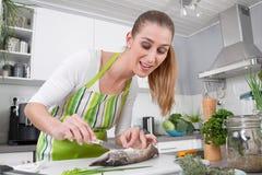Młodej kobiety kucharstwa ryba w kuchni obrazy royalty free
