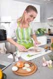 Młodej kobiety kucharstwo w kuchni zdjęcia stock