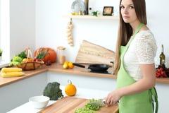 Młodej kobiety kucharstwo w kuchni Gospodyni domowa pokrajać świeżej sałatki fotografia royalty free