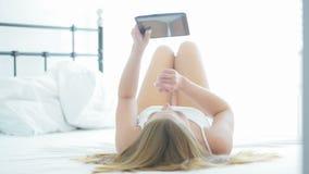 Młodej kobiety lying on the beach na jej łóżku używać peceta zbiory