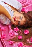 Młodej kobiety lying on the beach na różowym tle z kwiatami Obrazy Stock