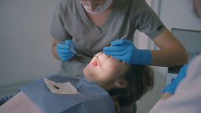 Młodej kobiety lying on the beach na stomatologicznym krześle i opowiadać z lekarką Dentysta robi stomatologicznemu badania kontr zbiory wideo
