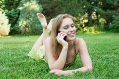 Młodej kobiety lying on the beach na trawie i opowiadać na telefonie fotografia stock
