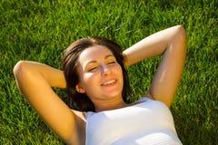 Młodej kobiety lying on the beach na zielonej trawie plenerowej zdjęcie stock