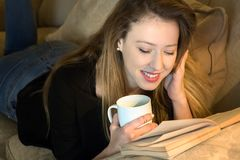 Młodej kobiety lying on the beach twarzy puszek czyta książkę i ma kawę obraz stock