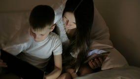 Młodej kobiety mama i jej syn ogląda ciekawego film na wpólnie pod koc pastylce i śmiechu zdjęcie wideo