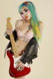 Młodej kobiety mienia gitara nad barwionym tłem Zdjęcia Stock