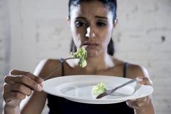 Młodej kobiety mienia naczynie z niedorzeczną sałatą jak jej karmowego symbol szalony diety odżywiania nieład zdjęcia royalty free