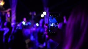 Młodej kobiety mienia smartphone w rękach, mknącym vide i patrzeć cyfrowego pokazu, Tłum bawi się przy żywym na wolnym powietrzu zbiory