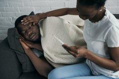 młodej kobiety mienia termometr i sprawdzać czoło chory chłopak zdjęcie royalty free