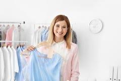 Młodej kobiety mienia wieszak z suknią fotografia stock