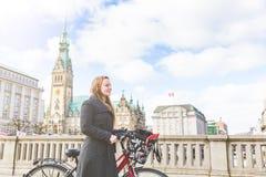 Młodej kobiety mienie i odprowadzenie rower w Hamburg obraz royalty free