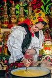 Młodej kobiety mieszanki polenta w wielkim garnku obrazy royalty free