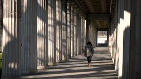 Młodej kobiety nastoletnia dziewczyna mieszał biegową żeńską jest ubranym kamuflaż kurtkę, chodzi przez kolumny przejścia podczas zdjęcie wideo