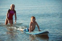 Młodej kobiety nauczanie surfuje jej syna w oceanie w słonecznym dniu Fotografia Stock