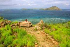 Młodej kobiety obsiadanie na ławce przy punktem widzenia na Kanawa wyspie Obrazy Stock