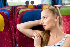 Młodej kobiety obsiadanie na autobusie zdjęcia stock