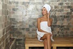 Młodej kobiety obsiadanie na drewnianej ławce w solankowym sauna obrazy royalty free