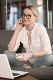 Młodej kobiety obsiadanie na kanapie, opowiada na telefonie i ono uśmiecha się Obraz Stock