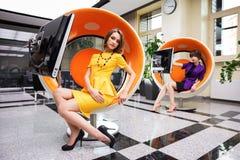 Młodej kobiety obsiadanie na komputerowym krześle w biurze Zdjęcia Stock