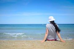 Młodej kobiety obsiadanie na piasku i patrzeć morze Obraz Royalty Free