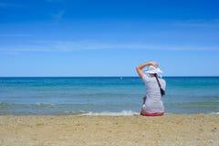 Młodej kobiety obsiadanie na plażowym i patrzeć morze Zdjęcie Royalty Free