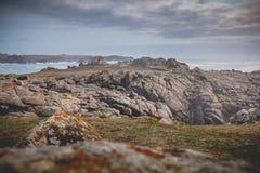 Młodej kobiety obsiadanie na skałach wyspa Yeu obraz stock