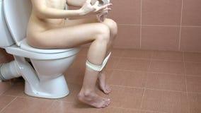 Młodej kobiety obsiadanie na toalecie w łazience i bierze papier toaletowego w ręce Use toaleta zbiory