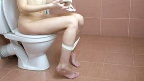 Młodej kobiety obsiadanie na toalecie w łazience i bierze papier toaletowego w ręce Use toaleta zbiory wideo