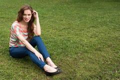 Młodej Kobiety obsiadanie na trawie zdjęcie stock