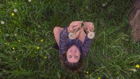 Młodej kobiety obsiadanie na trawie przy latem zbiory wideo