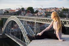 Młodej kobiety obsiadanie przeciw tłu Dom Luis Porto, przerzucam most Zdjęcie Stock