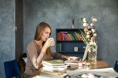 Młodej Kobiety obsiadanie przy biurem, Pije kawę Zdjęcie Stock