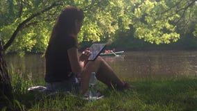 Młodej kobiety obsiadanie rzeką w parku i używa zbiory