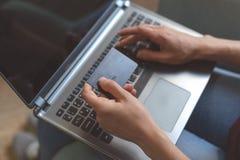 Młodej kobiety obsiadanie w kawiarni i używać laptopu mienia banka kartę w ręce fotografia royalty free