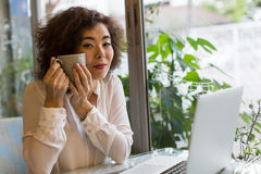 Młodej kobiety obsiadanie w kawiarni z laptopem i filiżanką herbata w jego ręki Zdjęcie Royalty Free