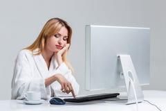 Młodej kobiety obsiadanie w używać komputerze i stole Zdjęcia Royalty Free
