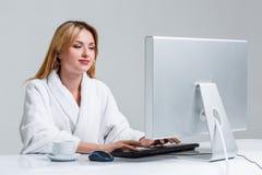 Młodej kobiety obsiadanie w używać komputerze i stole Fotografia Royalty Free