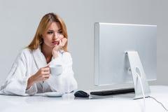 Młodej kobiety obsiadanie w używać komputerze i stole Zdjęcie Stock