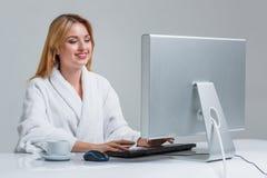 Młodej kobiety obsiadanie w używać komputerze i stole Fotografia Stock